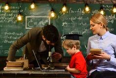 听的人看在膝上型计算机显示观看的培训班和它,殷勤老师谈话与她的学生  免版税库存照片