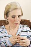 听的音乐前辈妇女 免版税库存照片