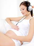 听的音乐孕妇 免版税库存图片