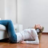 听的音乐微笑的妇女年轻人 免版税库存照片
