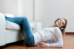 听的音乐微笑的妇女年轻人 库存图片