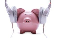 听立体声耳机的滑稽的存钱罐 免版税图库摄影