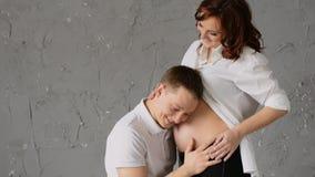 听英俊的年轻的人他怀孕的妻子的腹部 年轻妻子在头轻拍他 笑 慢的行动 股票录像