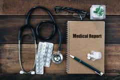 听诊器、医学药物和笔记本有医疗报告词的在它的盖子 库存照片
