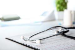 听诊器、心电图和形式在桌,特写镜头上 库存图片