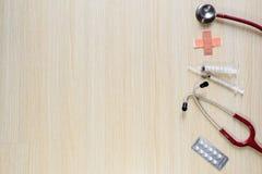听诊器、注射器、医学和膏药顶视图在木 免版税库存图片