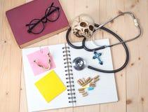 听诊器、笔访和头骨 免版税库存照片