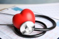 听诊器、红心和心电图在桌上 免版税库存照片