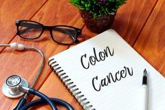 听诊器、镜片、植物、笔和书写与结肠癌在木背景,健康概念 库存照片