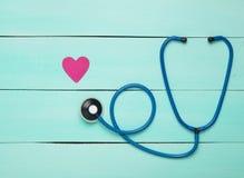 听诊器和心脏在一张蓝色木桌上 诊断的心血管病心脏病学设备 顶视图 平的位置 库存图片