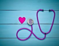 听诊器和心脏在一张蓝色木桌上 诊断的心血管病心脏病学设备 顶视图 平的位置 免版税库存图片