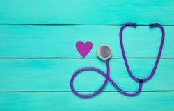 听诊器和心脏在一张蓝色木桌上 免版税库存图片