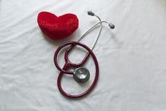 听诊器和心脏在白色背景计算 库存照片