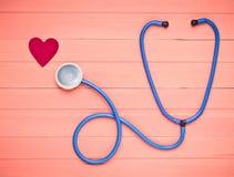 听诊器和心脏在粉红彩笔木桌上 诊断的心血管病心脏病学设备 顶视图 平的位置 库存照片