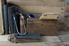 听诊器和案件在一张老书桌上 医疗杂志和med 免版税库存图片
