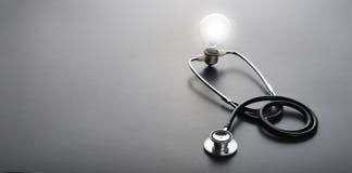 听诊器和电灯泡光在黑背景 免版税库存图片