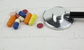 听诊器和疗程在描述心脏病学咨询的ECG板料  免版税图库摄影