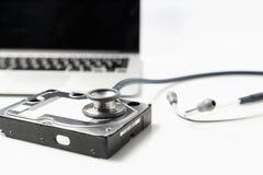 听诊器和硬盘驱动器在白色背景 计算机硬件诊断和修理概念 库存照片