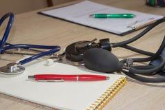 听诊器和笔在病历 身体检查的概念图象 库存图片