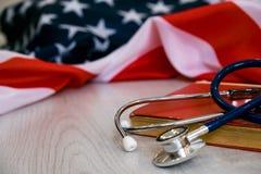 听诊器和红色书特写镜头照片在美国国旗 医学美国 登记概念教育查出的老 医疗程度 免版税库存照片