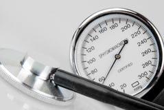 听诊器和血压计在白色 免版税库存照片
