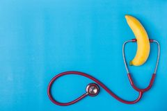 听诊器和黄色香蕉在蓝色背景 对人阴茎 图库摄影