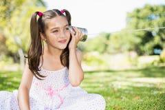 听通过锡罐电话的女孩 库存照片