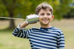 听通过锡罐电话的男孩 免版税图库摄影