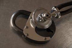 听金属表面上的一把锁的听诊器 库存图片