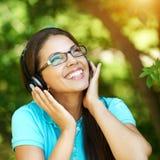 听音乐佩带的耳机的美丽的女孩 免版税库存照片