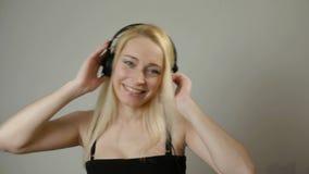 听音乐佩带的耳机的迷人的妇女40s 股票录像