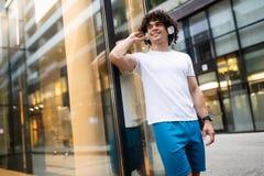 听音乐和休息的年轻适合的人在锻炼以后 免版税图库摄影