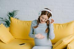 听音乐和跳舞的愉快的孕妇 免版税图库摄影