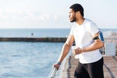听音乐和饮用水的运动员在码头 免版税库存图片