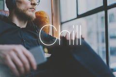 听音乐现代顶楼演播室的特写镜头照片英俊的有胡子的人耳机 供以人员坐在葡萄酒椅子,拿着smartphon 图库摄影