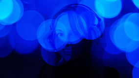 听音乐蓝色defocused背景的可爱的少妇 免版税图库摄影