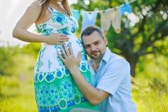 听他怀孕的妻子的腹部的愉快的未来父亲 库存图片