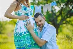 听他怀孕的妻子的腹部的愉快的未来父亲 免版税库存图片