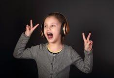 听滑稽的做鬼脸的孩子的女孩音乐,唱歌在wireles 免版税库存图片
