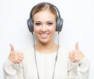 听年轻美丽的妇女从耳机的音乐 免版税库存照片