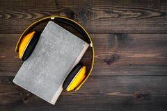 听audiobook概念 在一本书的耳机在黑暗的木背景顶视图拷贝空间 库存图片