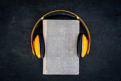 听audiobook概念 在一本书的耳机在黑背景顶视图 免版税库存照片