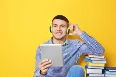 听audiobook的人通过耳机 免版税库存图片