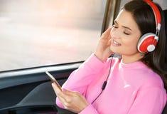 听audiobook的妇女通过耳机 免版税库存照片