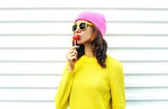 吮在五颜六色的衣裳的画象时尚相当凉快的女孩棒棒糖在戴桃红色帽子黄色太阳镜的白色背景 免版税库存照片
