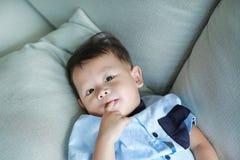 吮在嘴的可爱的矮小的亚裔男婴手指说谎在灰色沙发 图库摄影