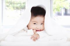 吮手指的亚裔婴孩在毯子或毛巾下 免版税库存图片