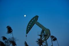 吮机器和月亮日出的油 库存图片