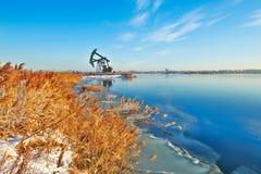吮机器和芦苇湖边的油 免版税库存照片