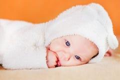 吮他的手指的逗人喜爱的矮小的婴孩 免版税库存图片